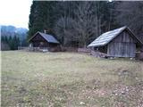 Slovenske planine v vseh letnih časihVišje naletim še na dve leseni stavbi. Za kočami se poti združita in od tu poteka pot po levem robu planine. Pašne povšine so ograjene..