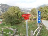 V vasi Tolminske Ravne je označeno parkirišče, pot nadaljujemo čez travnik.